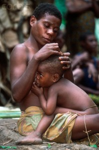 2002 --- A woman of the BaAka tribe, an indigenous hunter-gatherer group located throughout Cameroon and the Central African Republic, grooms her child while nursing. --- Image by © Martin Harvey/CORBIS